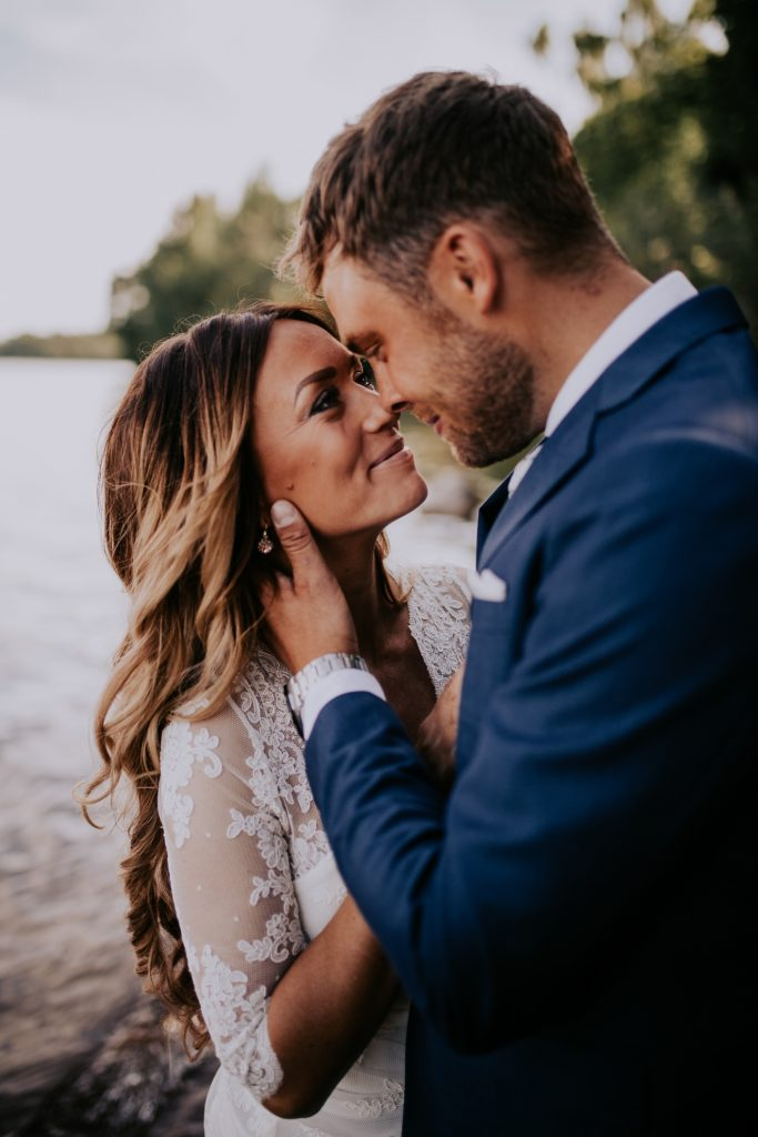 Kärleksfullt porträtt på brudpar vid ett sommarbröllop i Hjo