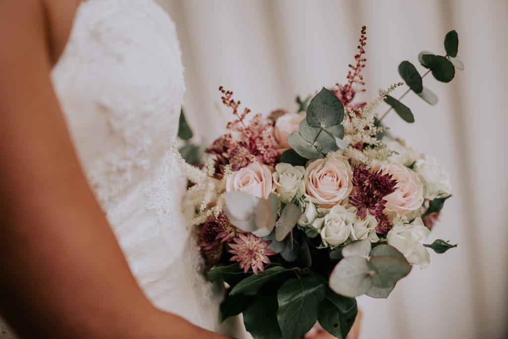 Vacker modern brudbukett med eukalyptus och rosa rosor
